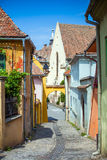 Old stone paved street with tourists from Sighisoara Stock Photo