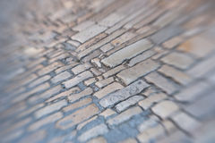 Old stone pavement background. Sharp in the middle and blurred to the edges. Tilt-shift lens shot Stock Image
