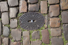 Old stone pavement with metal cover. Historic stone pavement, metal cover, street in Prague stock photo