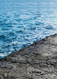 Old stone pier over water, close-up Royalty Free Stock Photo