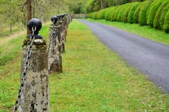 Old stone posts with iron chain link fence Stock Photography