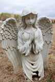 Old stone prayerful angel at graveside Stock Photos