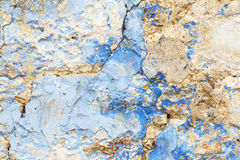 Old stone rustic cracked wall painted in blue paint as decay tex. Old stone rustic cracked wall rough painted in blue paint as decay texture background Stock Photography