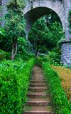Old stone stairs among the grass. And stone arc. Park landscape Royalty Free Stock Photo
