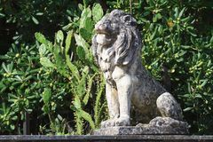 Old stone statue of a lion in the garden Stock Image