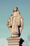 Old stone statue of the Virgin on the tombstone in the cemetery Royalty Free Stock Images