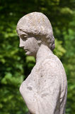 Old stone statue of a woman. In sunshine. Her left hand at the bosom, she looks thoughtful, sad, depressed or lonely. Antique weathered sculpture profile in a Royalty Free Stock Photography