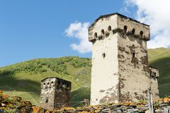 Old stone svan tower on street of Ushguli village in Svaneti, Georgia. Sunny day and sky with clouds background. royalty free stock photography