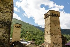 Old stone svan towers on street of Ushguli village in Svaneti, Georgia. Sunny day and sky with clouds background. stock photo