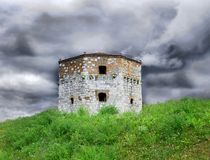 Old stone tower in Belgrade. Old tower of Belgrade fortress on green hill over storming sky Royalty Free Stock Photography