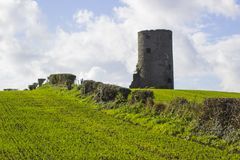 An old stone tower in a cut hay field on a farm in County Down in Ireland Royalty Free Stock Photos