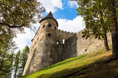 Old stone tower with loopholes. Castle in  Stara Lubovna. Old stone tower with loopholes surrounded by forest on the background of clouds and blue sky. Castle Stock Images