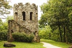 Old Stone Tower in Lush Green Scenery. An old stone tower in a tranquil setting of lush green forest - historic landmark, Clark Tower, in Winterset, Iowa Stock Photo