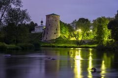 Old stone tower of medieval fortress and small church reflecting in river at night. Pskov fortifications, Russia stock photos