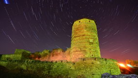 Old stone tower on starry night skyes background - startrail timelapse stock video footage