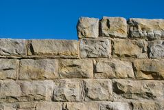 Old Stone Wall 03. Old sandstone wall with stepped or raised section and blue sky Stock Image