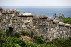 Old stone wall on the background of rocks and the sea royalty free stock image