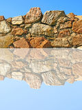 Old stone wall being reflected in water. Royalty Free Stock Photo