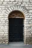 Old stone wall and black door, background texture Stock Photography