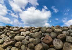 Old Stone wall with blue sky and clouds above. Old Stone wall buildt from the stones of the moraine Raet. Blue sky with clouds above the stone fence, from Royalty Free Stock Photos