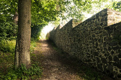 Old stone wall bordering the park. Old stone wall with serrate top bordering the park. There is fresh green vegetation in background Royalty Free Stock Photos