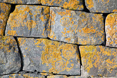 Old stone wall with bright lichen Stock Images