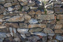 Old stone wall closeup texture. Invaded by moss, weathered, a rustic wall in Spain`s countryside Stock Image