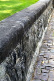 Old stone wall and cobblestone walkway Royalty Free Stock Photo