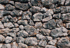 Old stone wall consisting of stacked naturally shaped loose rocks - background pattern stock photography