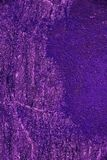 Old stone wall with cracked lilac color paint background. Cracks and scratches royalty free stock images