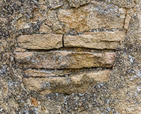 Old stone wall with crumbling plaster. Close-up Stock Photo