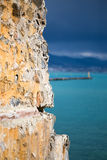 Old stone wall in focus and turquoise sea. Old stone castle wall in focus and blurred background with turquoise sea mountains and dark sky portrait layout shot Stock Photo