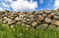 Old Stone wall with green grass in front and blue sky with clouds above. Old Stone wall buildt from the stones of the moraine Raet. With green grass in front and Royalty Free Stock Photo