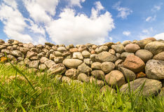Old Stone wall with green grass in front and blue sky with clouds above. Old Stone wall buildt from the stones of the moraine Raet. With green grass in front and Stock Photos