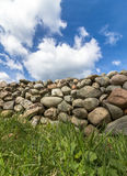 Old Stone wall with green grass in front and blue sky with clouds above, vertical image. Old Stone wall buildt from the stones of the moraine Raet. With green Royalty Free Stock Photos