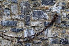 Old stone wall with hook and chains Stock Photos