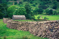 Old stone wall and a house in the Lake District, UK Stock Images