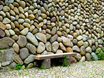 Old stone wall. A wall made by stones with a wooden bench in the front in Yunhe country Lishui city zhejiang provinceChina royalty free stock photos