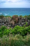Old stone wall overlooking the ocean Stock Photos