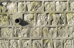 Old stone wall with pipe for drainage Stock Image