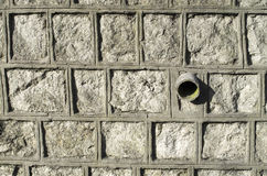 Old stone wall with pipe for drainage Royalty Free Stock Photo