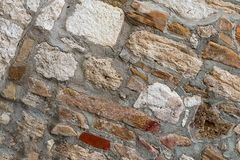 Old stone wall rectangular square cobblestones beige brown in cement-base background urban stock image