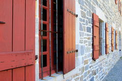 Old stone wall with red shuttered windows Royalty Free Stock Image