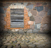 Old stone wall and window. Covered with wooden planks Stock Photos