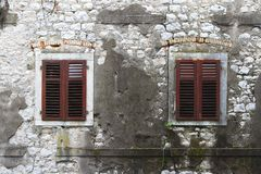 Old stone wall and windows shuttered closeup Royalty Free Stock Photography