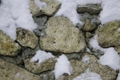 A old stone wall in winter under the snow. Stones under the snow royalty free stock images