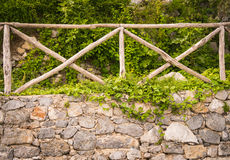 Old stone wall with wooden fence on it Stock Photos