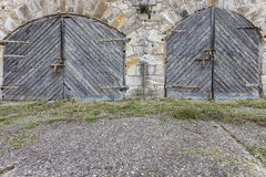Old stone wall and wooden gates Stock Photography