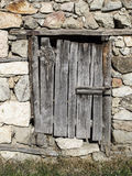 Old stone wall with wooden padlocked door Royalty Free Stock Photo