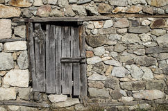 Old stone wall with wooden padlocked door Stock Image